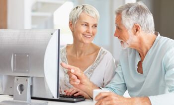 A senior man teaching a senior woman how to use the computer